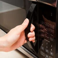 hand opening a microwave oven door to reheat pasta