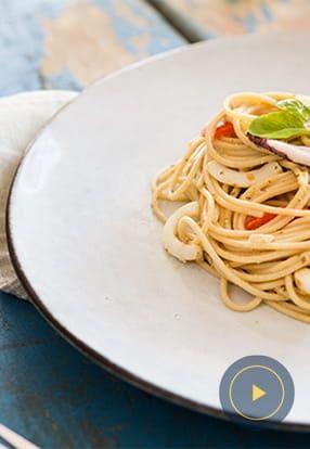 Polnozrnati špageti z genovskim pestom, lignji in češnjevci